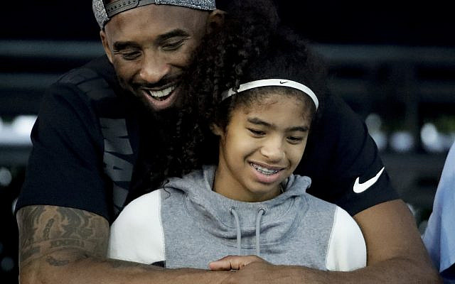 In this July 26, 2018 file photo former Los Angeles Laker Kobe Bryant and his daughter Gianna watch during the US national championships swimming meet in Irvine, Calif. Bryant, the 18-time NBA All-Star who won five championships and became one of the greatest basketball players of his generation during a 20-year career with the Los Angeles Lakers, died in a helicopter crash Sunday, Jan. 26, 2020. Gianna also died in the crash. She was 13. (AP Photo/Chris Carlson)