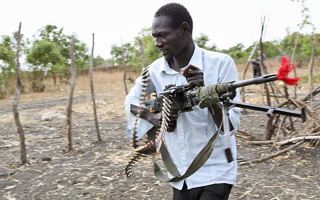 ILLUSTRATIVE: An opposition fighter In South Sudan walks with his weapon. Sunday, Jan. 21, 2018. (AP/Sam Mednick)