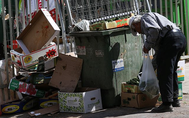 Illustrative: An elderly man searches among the garbage near the food market in the central Israeli city of Petah Tikva, June 24, 2015. (Nati Shohat/FLASH90)