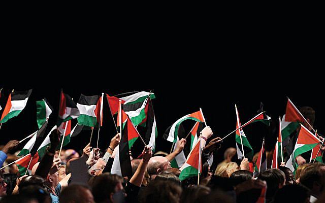 Delegates hold up Palestinian flags during a debate at Labour party conference, 2018. (Photo by Oli SCARFF / AFP)        (Photo credit should read OLI SCARFF/AFP/Getty Images via Jewish News)