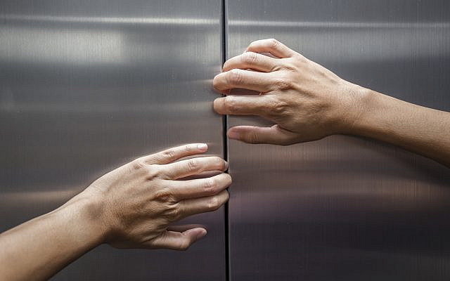 Illustrative. A woman tries to open the doors of a closed elevator. (iStock)