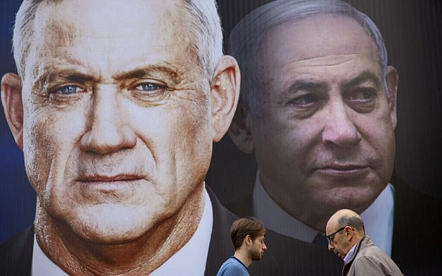 People walk past an election campaign billboard for the Blue and White party, the opposition party led by Benny Gantz, left, in Ramat Gan, February 20, 2020. Prime Minister Benjamin Netanyahu of the Likud party is pictured at right. (AP Photo/Oded Balilty)