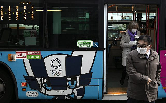 Passengers wearing masks get off a bus with the livery of Miraitowa, the official mascot of the Tokyo 2020 Olympics, in Tokyo, Thursday, March 5, 2020. (AP Photo/Jae C. Hong)