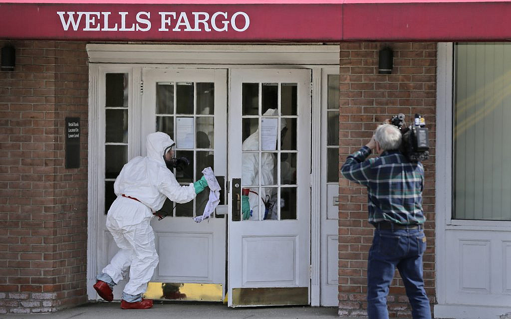 A cameraman records as a cleaning crew disinfects a bank in New Rochelle, N.Y., Wednesday, March 11, 2020. State officials are shuttering several schools and houses of worship for two weeks in the New York City suburb and sending in the National Guard to help with what appears to be the nation's biggest cluster of coronavirus cases, Gov. Andrew Cuomo said Tuesday. (AP Photo/Seth Wenig)