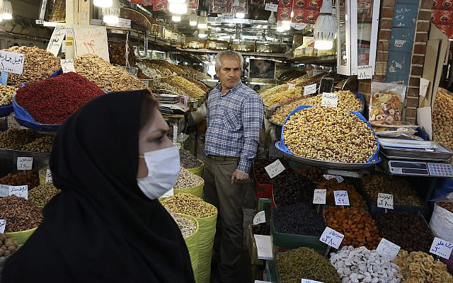 In Tehran's Grand Bazaar, Iran, March 17, 2020: A shopkeeper waits for customers as a woman wearing a face mask to help protect against the new coronavirus. (AP Photo/Vahid Salemi)