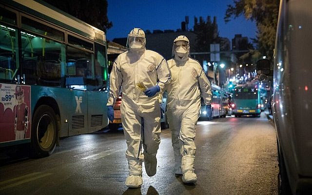 Magen David Adom workers, who wear protective clothing as a preventive measure against the coronavirus, arrive to test a patient with symptoms of COVID-19, in Jerusalem, March 16, 2020. (Yonatan Sindel/Flash90)