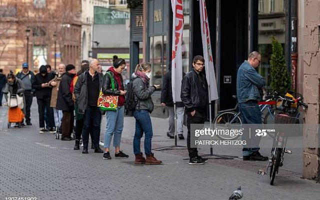 Customers wait in front of a supermarket in central Strasbourg, eastern France, on March 17, 2020, a few hours before the order of staying at home to all French citizens comes into effect, in order to avoid the spreading of the novel coronavirus. - In a live television address on March 16, 2020, French President Emmanuel Macron ordered people to stay at home to avoid spreading the new coronavirus, saying only necessary trips would be allowed and violations would be punished. France had already announced stringent new measures to close bars, restaurants and cinemas, which came after the closure of schools and a ban on large gatherings. (Photo by PATRICK HERTZOG / AFP) (Photo by PATRICK HERTZOG/AFP via Getty Images)