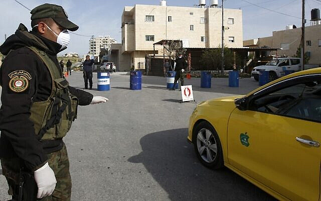 Palestinian security forces man a checkpoint at one of the entrances to the West Bank city of Bethlehem on March 10, 2020 currently under lockdown due to coronavirus. - The city of Bethlehem has been under lockdown since last week, after the first Palestinian cases of the deadly coronavirus were discovered there and authorities announced a state of emergency. (Photo by Musa Al SHAER / AFP)