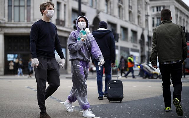 A man and woman wear protective face masks and gloves as they cross Oxford Street in central London on March 17, 2020. Britain on Tuesday, March 17, ramped up its response to the escalating coronavirus outbreak after the government imposed unprecedented peacetime measures prompted by scientific advice that infections and deaths would spiral without drastic action. (Photo by Tolga Akmen / AFP)
