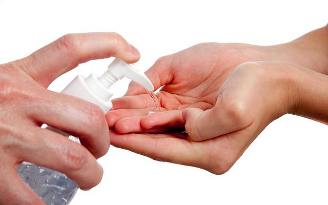 Illustrative. An adult dispensing hand-sanitizer to a child. (iStock)