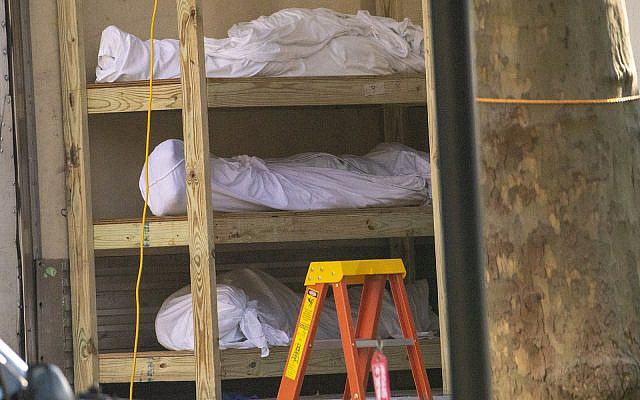 Bodies are seen on shelves in a refrigerated container at Kingsbrook Jewish Medical Center, Wednesday, April 8, 2020, in New York. (AP Photo/Mary Altaffer)