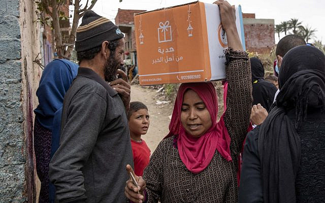 In Cairo, Egypt, a woman carries a carton filled with food distributed by the non-governmental organization Resala Nour Ala Nour to people who have been highly affected by the coronavirus outbreak. April 9, 2020. (AP Photo/Nariman El-Mofty)