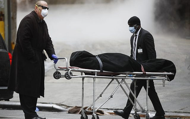 A funeral director wears personal protective equipment due to COVID-19 concerns while collecting a body at The Brooklyn Hospital Center, Thursday, April 9, 2020, in Brooklyn, New York. New York state posted a record-breaking number of coronavirus deaths for a third consecutive day even as a surge of patients in overwhelmed hospitals slowed, while isolation-weary residents were warned Thursday the crisis was far from over. (AP Photo/John Minchillo)