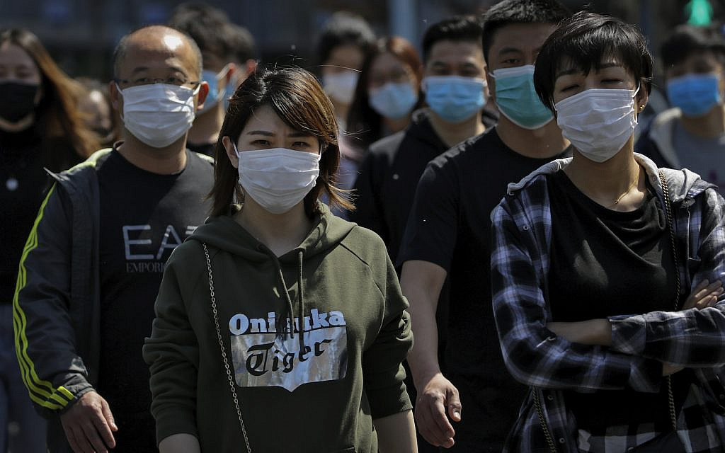 People wearing protective face masks to prevent the spread of the new coronavirus walk across a street in Beijing, Sunday, April 12, 2020. (AP Photo/Andy Wong)