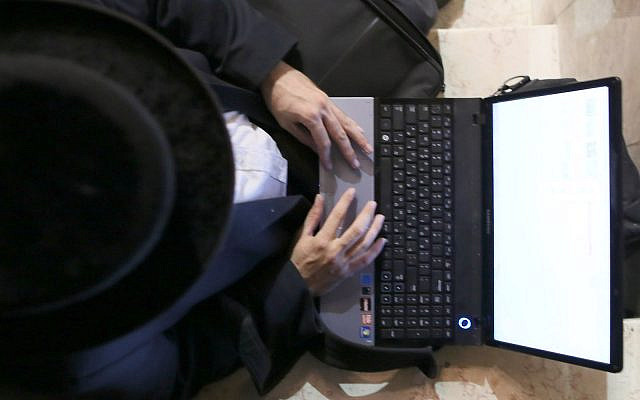 Illustrative: Ultra orthodox jewish photographer Moshe Friedman edits his pictures on a laptop, after photographing a wedding in the ultra orthodox neighborhood of Meah Shearim, in Jerusalem. August 28, 2012. (Nati Shohat/FLASH90)