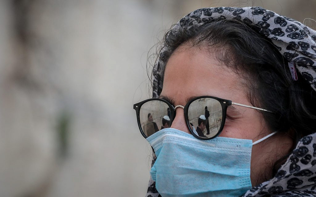Illustrative: A woman wears face mask for fear of the coronavirus as she attends a bar mitzvah, at the Western Wall, Judaism's holiest site, in Jerusalem's Old City on March 19, 2020. (Yossi Zamir/Flash90)