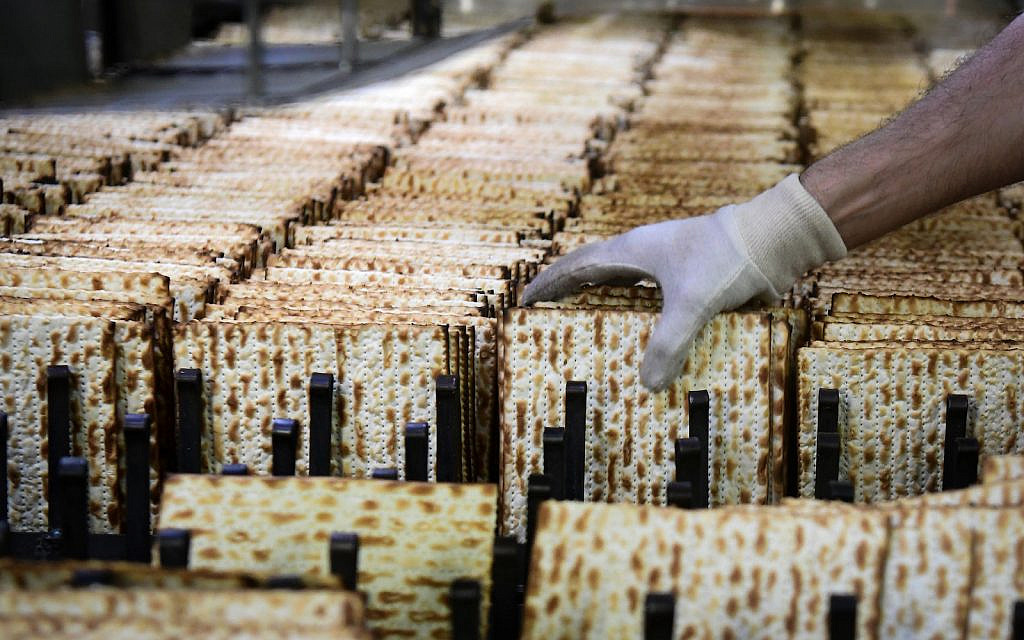"Workers prepare matzah, traditional unleavened bread eaten during the 8-day Jewish holiday of Passover, in ""Aviv Matzos"" Plant in Bnei Brak on March 24, 2020. (Yehuda Haim/Flash90)"