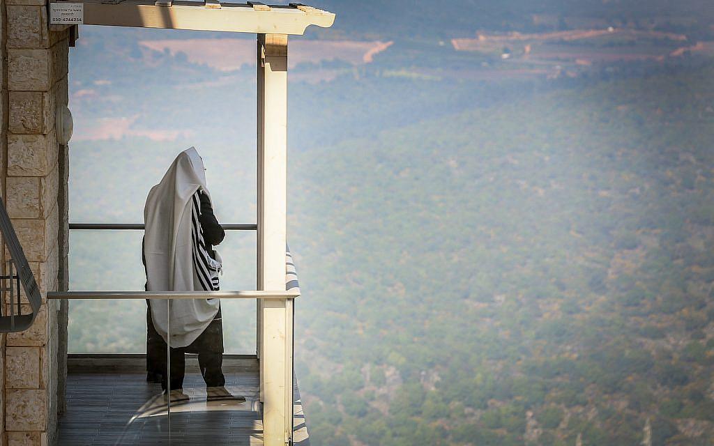 Illustrative: A Jewish man prays at his homes the city Safed, April 13, 2020. (David Cohen/Flash90)