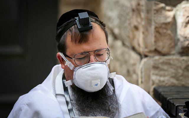 Illustrative: Jewish man prays outside the closed Rashbi gravesite in Meron, Northern Israel, on April 22, 2020. (David Cohen/Flash90)