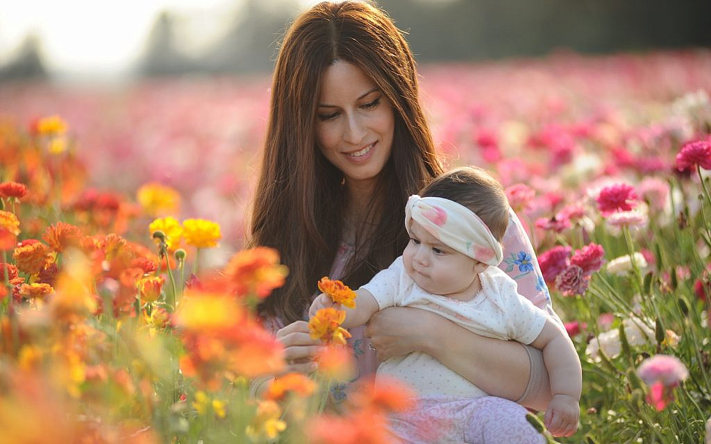 A mother holds her baby at a field of buttercup flowers near Kibbutz Nir Itzhak in southern Israel, on April 26, 2020.(Mendy Hechtman/Flash90)