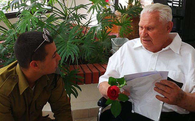 "A WIZO Parents' Home resident shares his life story with an IDF soldier as part of ""A Flower for a Survivor"") (Photo credit: Yonatan Sredni)"