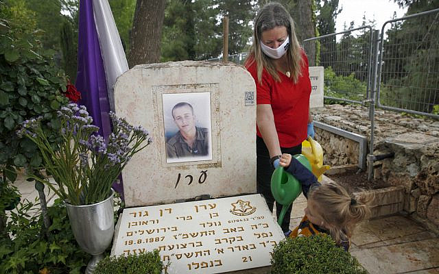 "Dr. Mary Dan-Gur, bereaved mother of Eran Z""L, killed in battle in Gaza in 2008, helps her son Or to tidy his brother's grave at the Military cemetery on Mt. Herzl in Jerusalem. (Ariel Jerozolimski)"