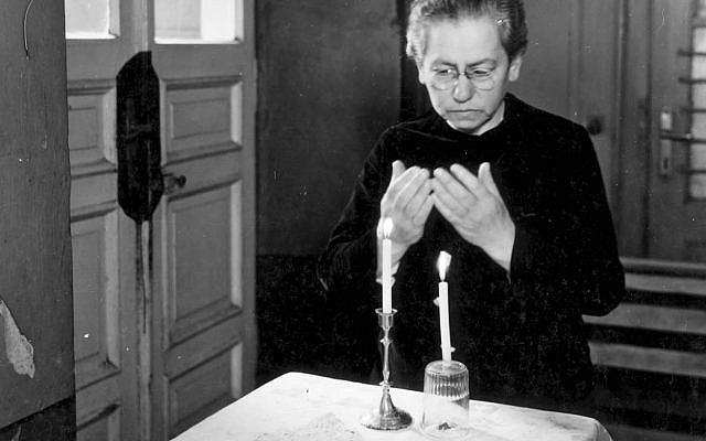 A woman at a displaced persons camp after the Holocaust lights Shabbat candles with what she has. (Source: Yad Vashem)