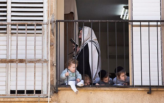 An ultra-Orthodox man prays at home, during a lockdown following the government's measures to help stop the spread of the coronavirus, in Bnei Brak, April 8, 2020. (AP Photo/ Oded Balilty)
