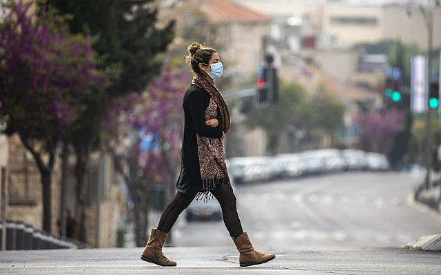 An Israeli woman with a face mask walks in Jerusalem on April 15, 2020. (Olivier Fitoussi/Flash90)