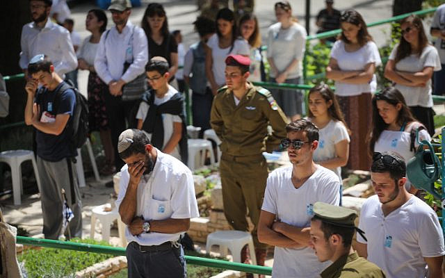 In a different year, when social distancing was not yet relevant: people stand in silence next to graves of Israeli soldiers at the Mt. Herzl military cemetery in Jerusalem, as a two-minute siren sounded across Israel, marking Memorial Day which commemorates Israel's fallen soldiers and victims of terror. April 18, 2018. (Miriam Alster/ Flash90)