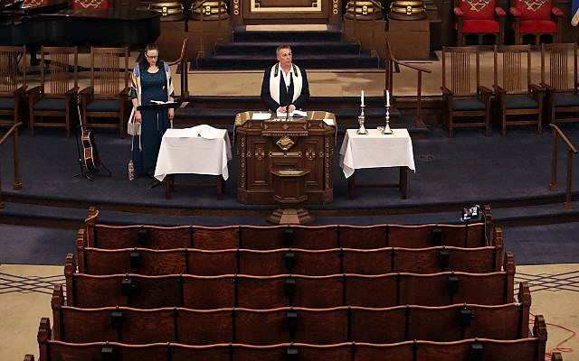 Illustrative: Rodef Shalom Rabbi Aaron Bisno, center, delivers his sermon with soloist Molly May, left, during an Erev Shabbat service that is being streamed live on Facebook. Friday, March 20, 2020. (AP Photo/Gene J. Puskar)
