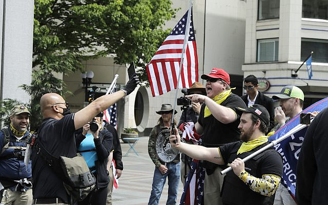 Members of a group wearing shirts with the logo of the far-right Proud Boys group at right, argue with a counter protester during a small protest against Washington state's stay-at-home orders, Friday, May 1, 2020, in downtown Seattle. (AP Photo/Ted S. Warren)