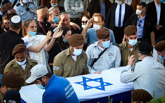 Family and friends watch as the coffin of IDF soldier Amit Ben Y'Gal is laid to rest in the military cemetery at Beer Yaakov on May 12, 2020.