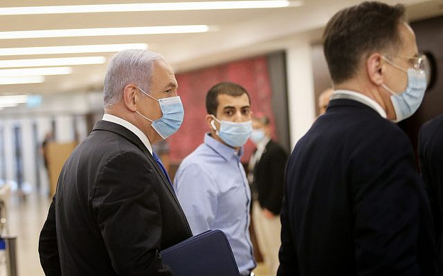 Prime Minister Benjamin Netanyahu walks in the Knesset after presenting the 35th government of Israel to the Knesset, May 17, 2020. (Alex Kolomoisky/POOL)