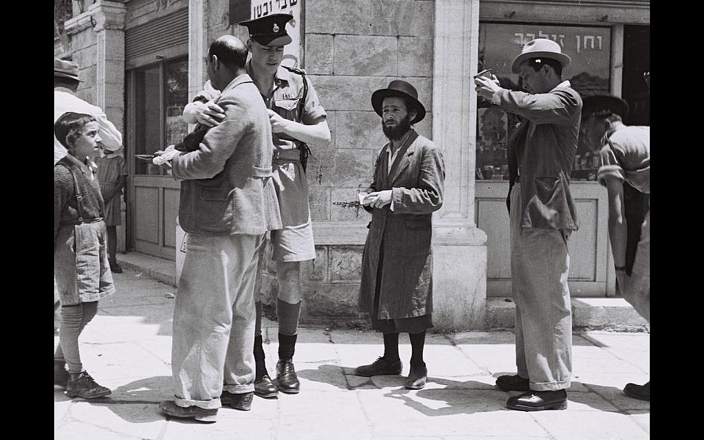 A British policeman checking papers of passers by on a street in Jerusalem, during the British Mandate, 1947 (Wiki Cc)