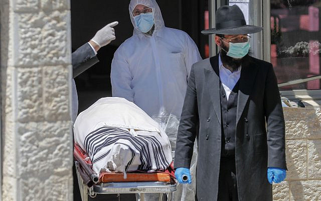 An Israeli rabbi walks alongside the body of Eliahu Bakshi-Doron, the former Sephardic chief rabbi of Israel, who died from complications of the coronavirus. (Ahmad Gharabli via Getty Images)