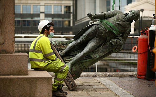 A worker sits down as they take down a statue of slave owner Robert Milligan at West India Quay, east London (Yui Mok/PA Wire via Jewish News)
