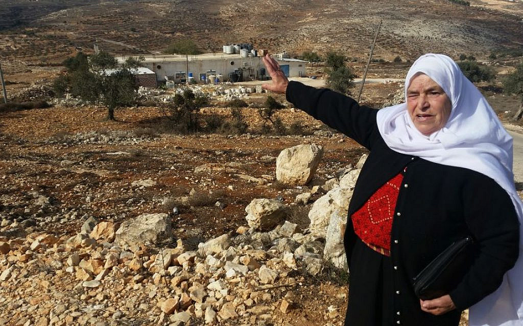Mariam Hammad, of nearby Silwad, points to a piece of land in the West Bank she says belongs to her but was taken by Israelis to build the outpost of Amona, November 2016 (Raphael Ahren/Times of Israel)