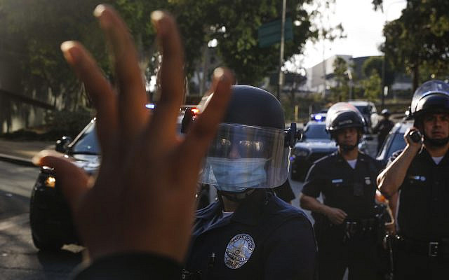 A protester holds up her hand while confronting police officers during a demonstration over the death of George Floyd, Friday, May 29, 2020, in Los Angeles. (AP Photo/Jae C. Hong)