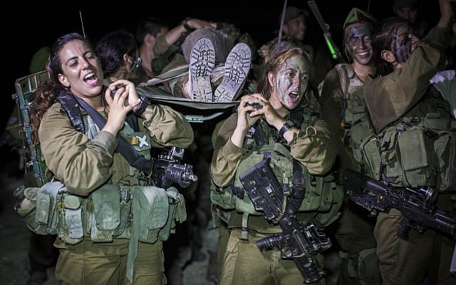 Soldiers of the Caracal Battalion seen cheering while carrying a fellow soldier on a stretcher at the end of their 16 Kilometer journey to complete their training course, in Tel Nitzan, southern Israel, near the border with Egypt, September 3, 2014. (Hadas Parush/Flash90)