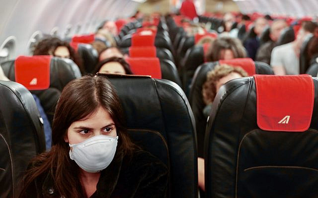 A woman wears a face mask for fear of the coronavirus on the flight from Ben Gurion International Airport to Rome's Fiumicino airport on February 21, 2020. (Nati shohat/Flash90)