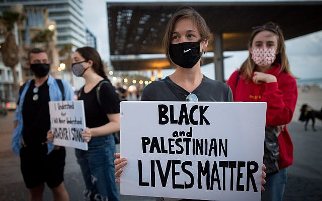 Israelis holds signs during a protest against the death in Minneapolis police custody of George Floyd outside the US consulate in Tel Aviv on June 02 2020 (Miriam Alster/Flash90)