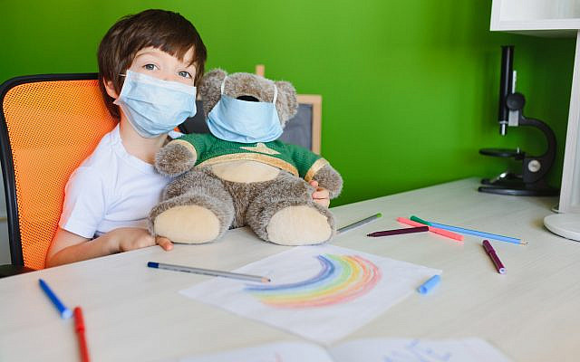 Kid in mask painting rainbow at home during coronavirus pandemic concept. Let's all be well. Stay at home Social media campaign. Children Chase the rainbow
