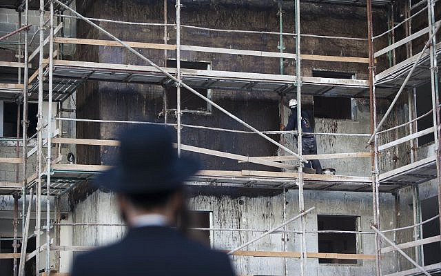 Illustrative: An ultra-Orthodox Jewish man watches a Palestinian worker at a construction site in the Gilo neighbourhood in southern Jerusalem, August 13, 2013 (Yonatan Sindel/Flash90)