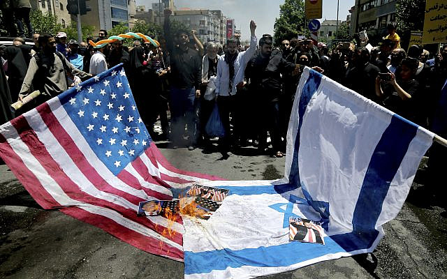 Iranian protesters burn Israeli and US flags in their annual anti-Israeli Al-Quds, Jerusalem, Day rally in Tehran, Iran, June 8, 2018. Iranians attended the rallies across the country to condemn Israeli occupation of Palestinian territories. (AP Photo/ Ebrahim Noroozi)