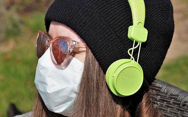 A woman wearing a protective mask with headphones (Pixaby/ivabalk)