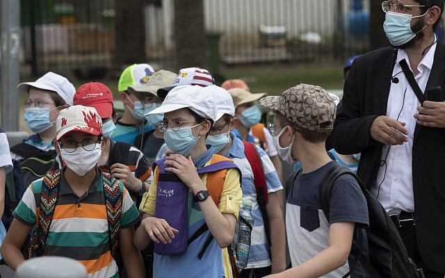 Israeli school children wear face masks to help prevent the spread of the coronavirus as they walk in Tel Aviv, July 6, 2020. (AP Photo/Sebastian Scheiner)
