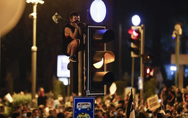 A protester holds flowers and sits on a traffic signal during a demonstration against the Prime Minister Benjamin Netanyahu, in Jerusalem, on July 23, 2020. (MENAHEM KAHANA / AFP)