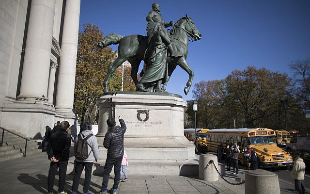 Visitors to the American Museum of Natural History in New York City look at a statue of Theodore Roosevelt, flanked by a Native American man and African American man, on November 17, 2017. The statue will be coming down after the museum's proposal to remove it was approved by the city (AP Photo/ Mary Altaffer/ File)