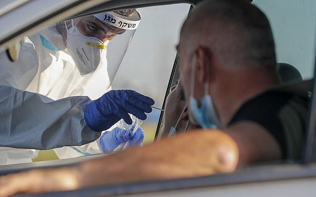 Illustrative. A Magen David Adom paramedic swabs a person for COVID-19 at a drive-thru testing site in the central city of Lod on July 15, 2020. (Ahmad Gharabli/AFP)